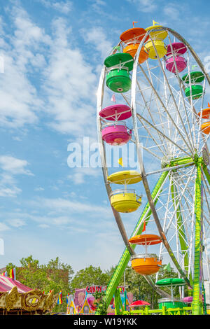 A colorful Ferris Wheel amusement ride in Traverse City, Michigan , part of the National Cherry Festival celebration . - Stock Image