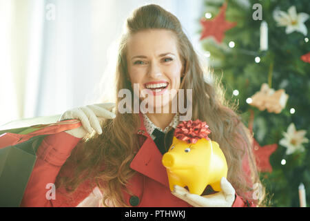 Portrait of happy young woman in red trench coat with shopping bags and yellow piggy bank near Christmas tree - Stock Image