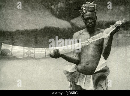 Trumpeter of the Mangbettu (Mangbetu) court, holding his carved horn modelled from an ivory tusk, Belgian Congo (now Democratic Republic of the Congo), Central Africa. - Stock Image