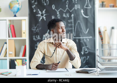 Young secondary school teacher sitting by desk and getting inspired while organizing next lessons - Stock Image
