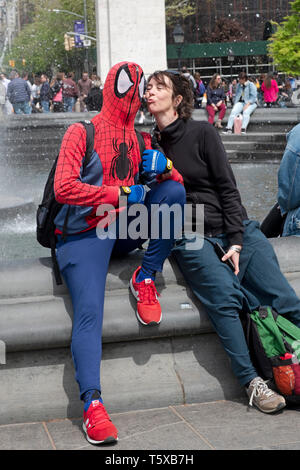 A street artist performer dressed as SPIDERMAN poses with a female Italian tourist in Washington Square Park, Manhattan, New York City. - Stock Image