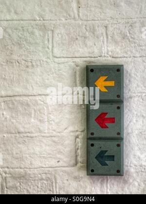 Coloured arrows on brick wall - Stock Image