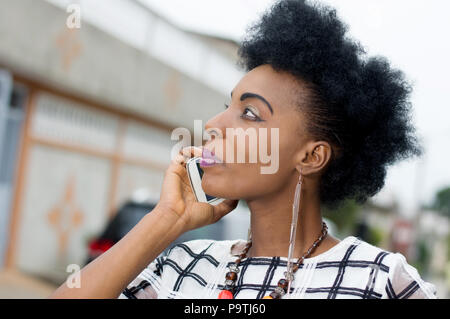 Close-up of a young woman on the phone and listening intently to the conversation - Stock Image