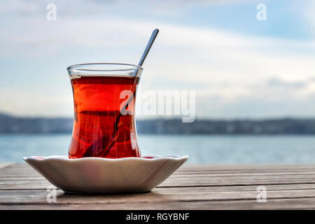 Turkish tea served in the typical manner, in a glass on a small saucer - Stock Image