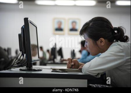 Des Nord coréens étudient à la grande maison des études du peuple de Pyongyang devant le portraits - Stock Image