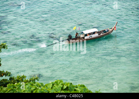 Thailand, Krabi, Ko Phi Phi Don. Long-tail boat in the clear waters of the Andaman Sea. - Stock Image