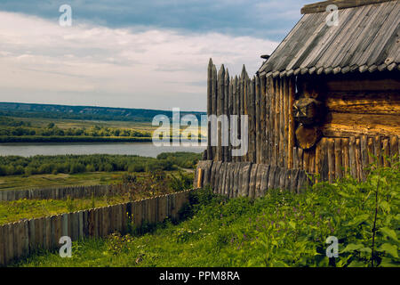 Wooden fence with pointed ends with a log cabin against the background - Stock Image