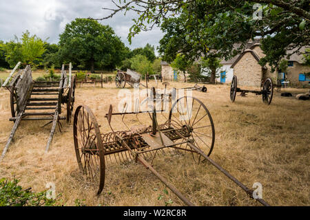 old carriages and tools standing on a dry meadow in Saint Lyphard - Stock Image