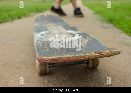 feet running behind a skateboard. - Stock Image