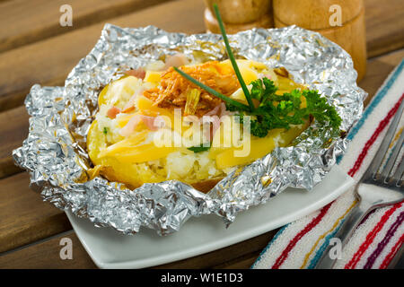 Delicious  baked in foil potatoes with filling of bacon, cheese and fried onion - Stock Image