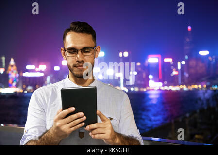 Man works with tablet computer against night city. Remote work concept. Hong-Kong, China - Stock Image