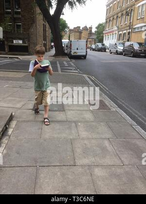 9 year old walking along the pavement while reading a book - Stock Image