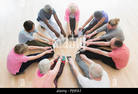 Active seniors stretching legs in circle in exercise class - Stock Image