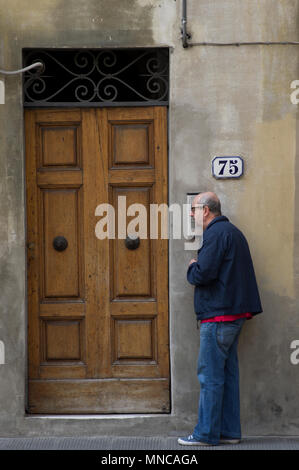 man listens at a door intercom after ringing the doorbell of number 75 in florence italy - Stock Image