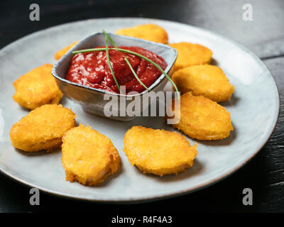 Soy nuggets on a plate, served with a spicy tomato dip. - Stock Image