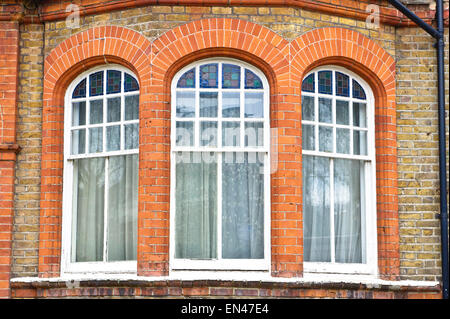 Arch windows in a red brick building in London, UK - Stock Image