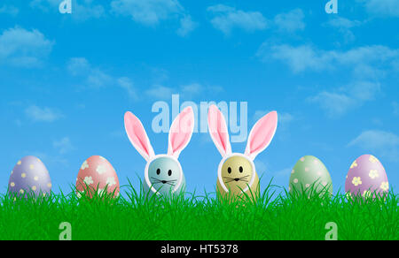 colorful pastel easter eggs with bunny ears in grass with blue sky background, copy space - Stock Image
