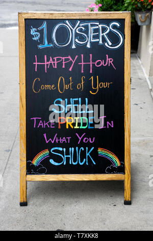 A sign with sexual innuendo outside a restaurant in Greenwich Village drawn during Gay Pride week. - Stock Image