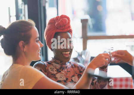 Happy young women friends taking alcohol shot in bar - Stock Image