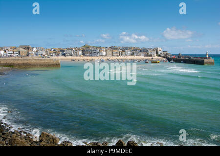 A view of St Ives harbour in the distance with its white lighthouse on Smeatons Pier, St Ives, Cornwall, UK - Stock Image