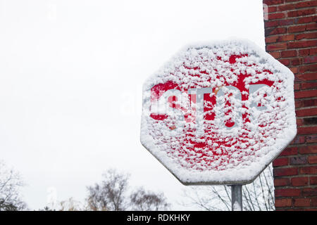 Stop traffic sign covered by snow warning of risk of car accident caused by snow - Stock Image