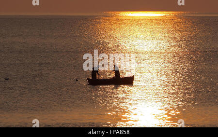 Fishermen from Portland as the evening sun sets over the calm sea of 'Lyme Bay', Dorset, UK - Stock Image