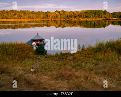 Salt Pond, Eastham, Cape Cod, Massachusetts, USA with a solitary boat moored in the water. - Stock Image