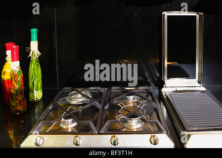 Bottles of pickles near a gas stove - Stock Image