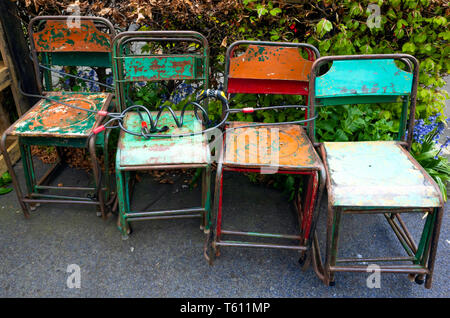 Eight old fashioned metal stackable chairs stored outside but locked with a cycle chain to avoid theft - Stock Image