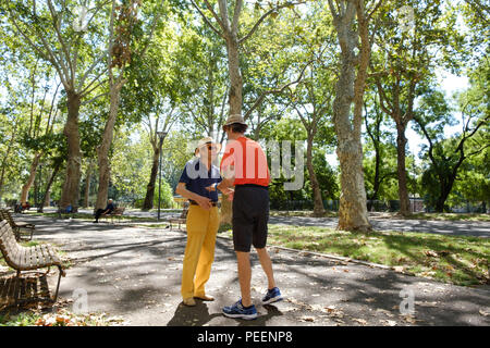 Colourfully dressed italian men both with straw hats meeting and greeting each other on a summers morning at the park. Piacenza, Italy. - Stock Image