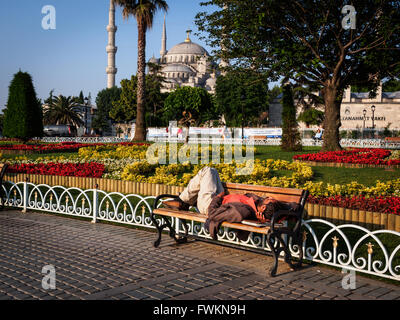 Homeless man sleeping in morning on bench in park in front of the Blue Mosque (Sultan Ahmed Mosque) in Istanbul, - Stock Image