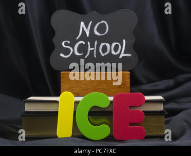 ICE in letters with NO SCHOOL on small chalkboard with books and black satin background. Icy weather conditions create danger and school closings. - Stock Image