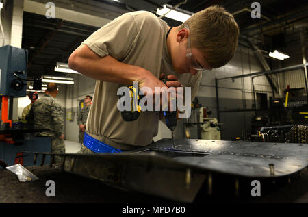 U.S. Air Force Airman 1st Class Daniel Meadows, 20th Equipment Maintenance Squadron aircraft structural maintenance apprentice, removes and replaces rivets on a gun door at Shaw Air Force Base, S.C., Feb. 8, 2017. Meadows replaced the rivets to restore the structural integrity of the piece so it could be reinstalled onto an F-16CM Fighting Falcon. (U.S. Air Force photo by Airman 1st Class Destinee Sweeney) - Stock Image