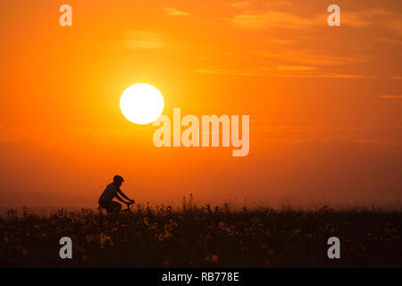 Woman riding bicycle on Nose Hill - Stock Image