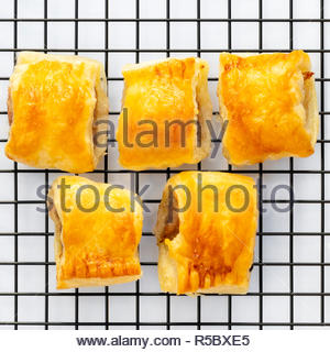 Homemade sausage rolls on a wire cooling rack, shot from above. - Stock Image