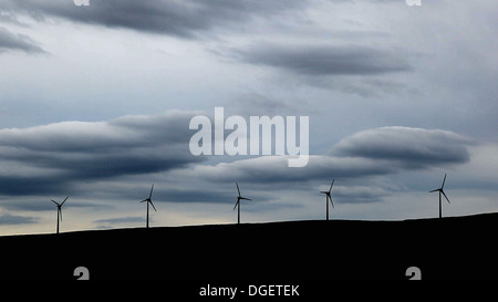 Five Wind turbines on a hill, heavy cloud behind. - Stock Image
