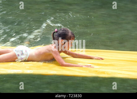 Seven Year Old Girl Playing on a Backyard Water Slide, 1990,  USA - Stock Image