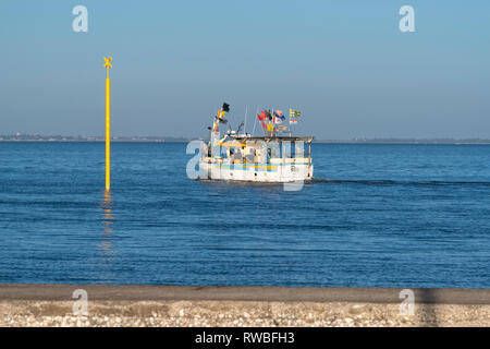 France, 2018, Small trawler navigates around a yellow, waterway marker, before - Stock Image