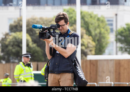 A cameraman holding a camera looking down the lens - Stock Image