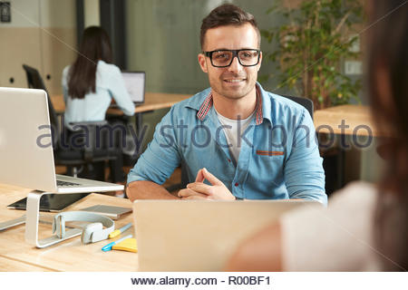 Smiling young man during meeting - Stock Image