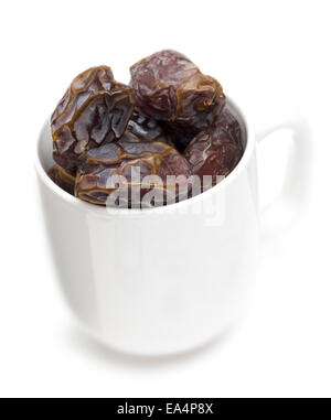 Cup of Medjool dates on white - Stock Image