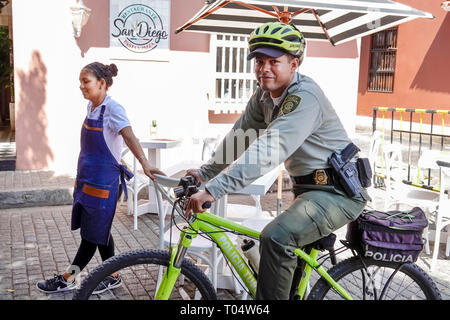 Cartagena Colombia Old Walled City Center centre Centro Parque de San Diego plaza Hispanic resident residents policia police bicycle officer helmet ar - Stock Image
