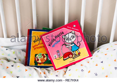 Poznan, Poland - November 8, 2018: Polish Kicia Kocia child book about cat doing some cleaning. Books are laying on a baby bed. - Stock Image