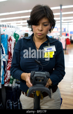 A female associate uses a Telxon handheld scanner to read EPC/RFID labels on clothing at a Walmart Supercenter in - Stock Image