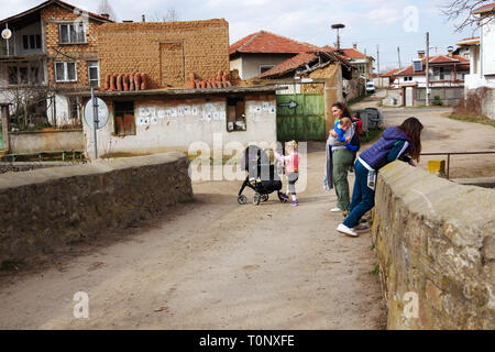 Turia, Bulgaria, March 9, 2019. There are masquerade games in the village to evict the evil. The masked are called Kukeri. Mother and her children exp - Stock Image