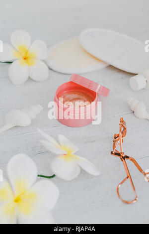 spa inspired set of scrub body lotions surrounded by flowers and seashells on light cooured wood, concept of luxury and organic products - Stock Image