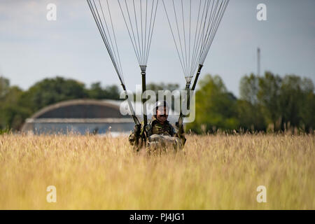 A Romanian air force paratrooper lands on a dropzone at Boboc Air Base, Romania, Aug. 23, 2018. The paratrooper jumped out of a U.S. Air Force C-130J Super Hercules aircraft as part of Carpathian Summer 2018, a bilateral training exercise designed to enhance interoperability and readiness of forces by conducting combined air operations with the Romanian air force. (U.S. Air Force photo by Senior Airman Devin Boyer) - Stock Image
