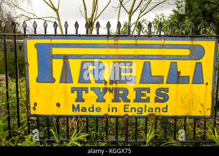 Old metallic advertisement for Pirelli motor tyres seen at a heritage steam railway station in Somerset UK - Stock Image