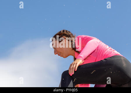 Young woman in a pink top against a blue sky - Stock Image