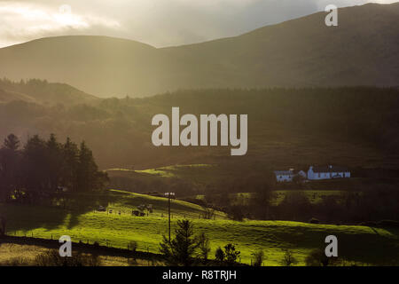 Ardara, County Donegal, Ireland. 18th December 2018. A small farmhouse cottage is seen through light passing by stormclouds on a day of heavy showers and some sunny spells. Credit: Richard Wayman/Alamy Live News - Stock Image